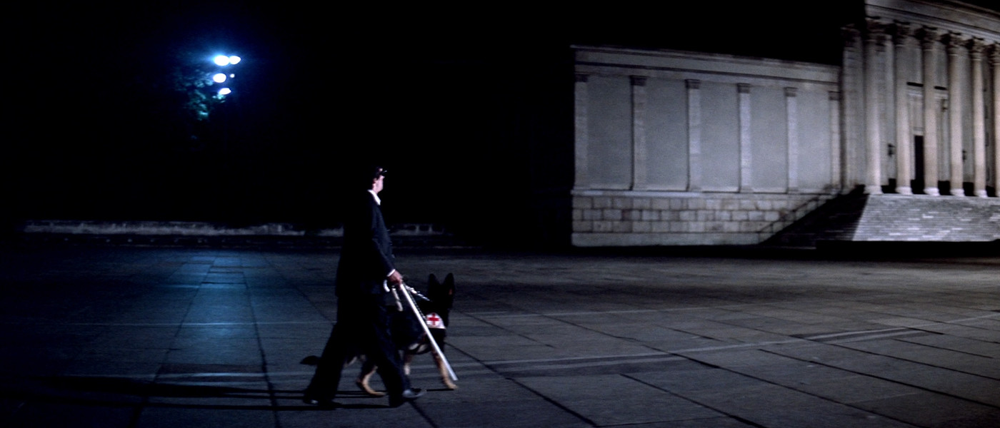 Plaza scene with white cane and red cross from Suspiria